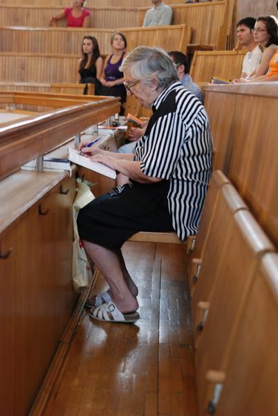 o doamnă înaintată vîrstă își notițe de la balconul bisericii
